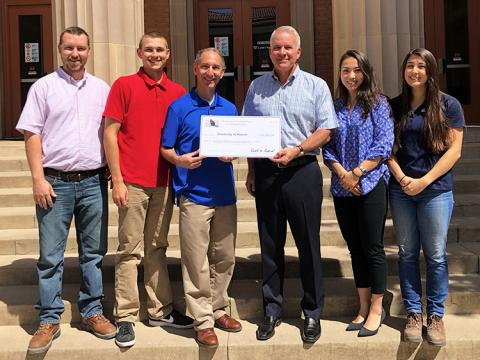 Two men, flanked by two male students on the left and two female students on the right, hold a check for $50,000 intended for the Beavers Scholarship Endowment