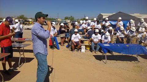 A man wearing a baseball cap, standing to the left of the frame, speaks to a gathered crowd, all wearing white T-shirts and hard hats