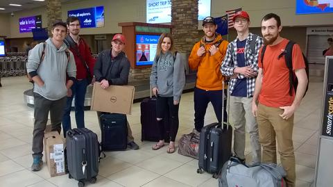 A group of students pose with their luggage in an airport with information screens in the background