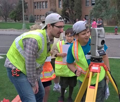 A man in a baseball cap and a yellow safety vest stands to the side of a boy, also wearing a yellow safety vest, as he peers through a theodolite