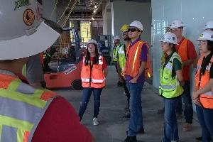 A man wearing a white hardhat and a yellow safety vest stands in the foreground and addresses a group of students who are also wearing safety gear in a partially constructed building.
