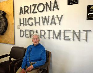 An older woman with white hair and a blue sweater sits in a chair in front of a sign that reads Arizona Highway Department.