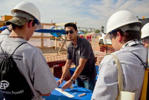 A student in a blue shirt and sunglasses stands at a table, explaining instructions to three younger students wearing hardhats and gray shirts.