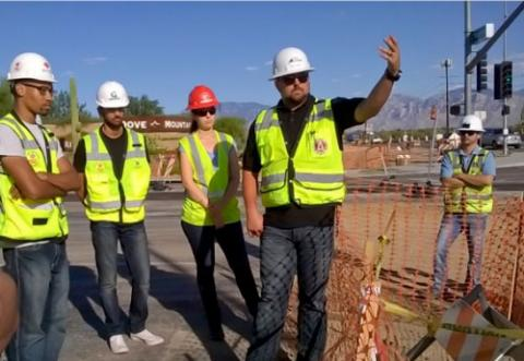 A man in a white hardhat and yellow safety vest gestures at a construction site, explaining a concept to the three students in safety gear behind him.