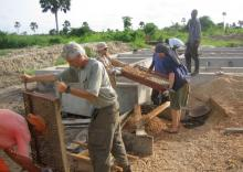 Volunteers with the UA chapter of Engineers Without Borders assist villagers in Ghana with rock sieves to help filter water.