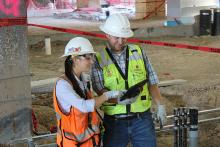 A female and male engineering student, both wearing safety gear, consult a clipboard while standing in a construction area