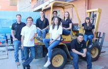 Four female and five male students sit on and lean against a yellow construction forklift