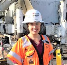 A woman in a white hardhat and an orange safety vest stands in front of construction equipment