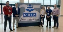 """Four male students and one female student standing either side of a large poster that reads """"DBIA Silver Anniversary"""""""