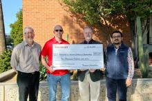 Four men holding a giant check while standing before a brick wall.