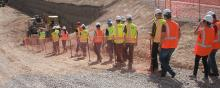 A line of people in hardhats and orange safety vests walking down a hill toward construction vehicles