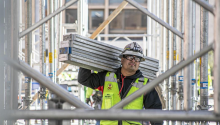 A man wearing a construction vest carries four metal beams on a construction site.