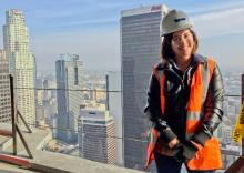 Woman standing in hardhat and orange safety vest on the balcony of a tall building, with skyscrapers behind her