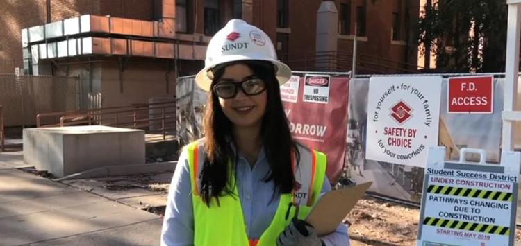 Andrea Flores in white Sundt hard hat and reflective vest, standing by UA Student Success District construction site