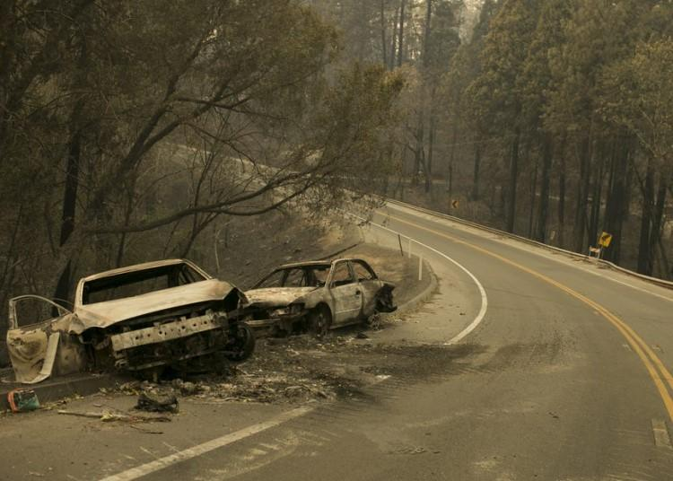 Two burned-out cars, pushed to the side of a two-lane paved road.