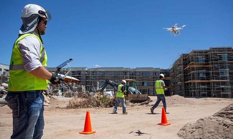 A man in a hard hat and reflective vest holds a control panel while a drone flies in front of him at a constructino site
