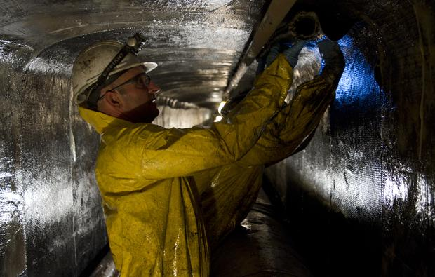 Workers apply carbon fiber mats soaked in epoxy resin to stabilize the utility tunnels that crisscross underneath the UA campus. (Photo: Carina Johnson/UANews)