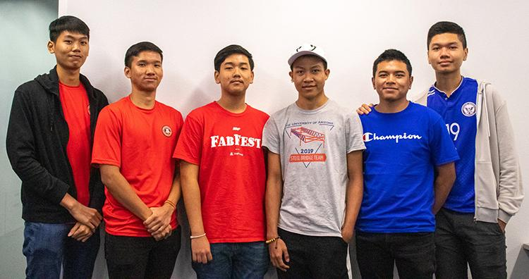 Six Cambodian students wearing UA red and blue shirts stand in front of a white wall