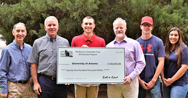 "A group of six people stand in front of a tree holding an oversized check that reads ""The Beavers Charitable Trust Scholarship Program."" The check is made out to the University of Arizona in the amount of $100,000."