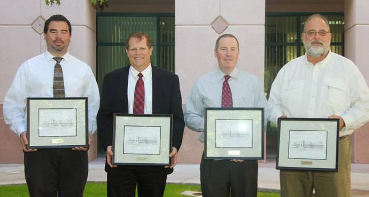 Four men in dress shirts and ties stand in a line, holding certificates in frames