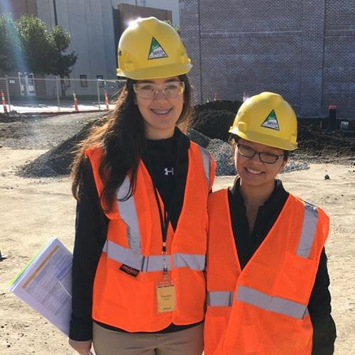 Lisette Flores and Rosa Juvera pose together in hard hats and reflective vests at a construction site