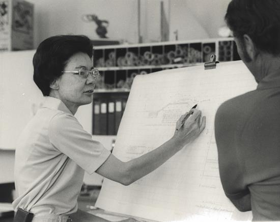 Black and white photo of a woman sketching an architectural drawing while someone else looks over her shoulder