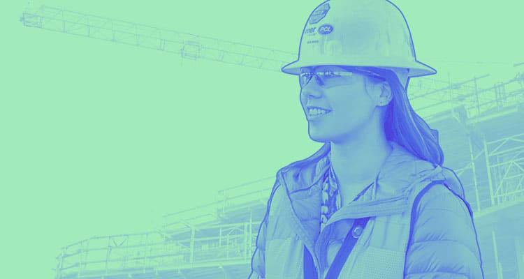 High-contrast photo of Katie Wood wearing a hard hat in only blue and green tones